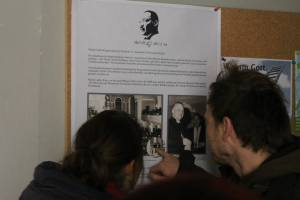 A couple is reading about Dr. Martin Luther King Jr visiting a church in east Berlin, while the wall was standing.